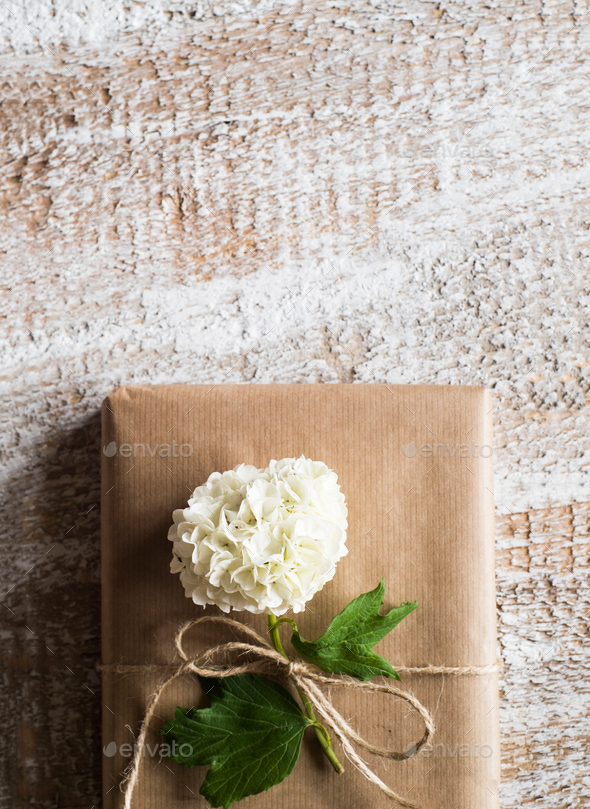 Present wrapped in brown paper, lilac flower laid on it. - Stock Photo - Images
