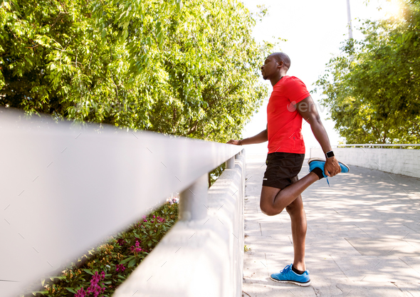 Afro-american runner in the city stretching his legs. - Stock Photo - Images