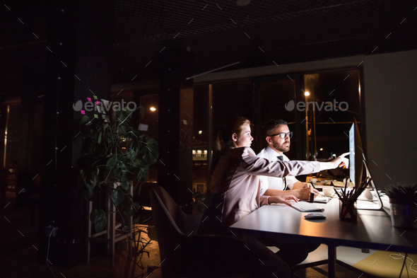 Businesspeople in the office at night working late. - Stock Photo - Images