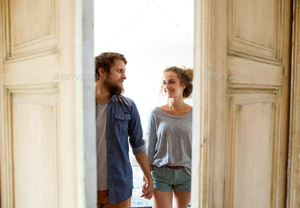 Couple moving in new house, entering through the door. - Stock Photo - Images