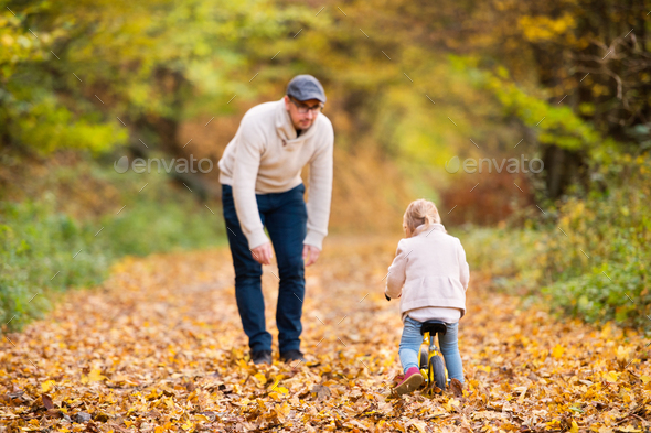 Father with little daughter cycling in autumn park. - Stock Photo - Images