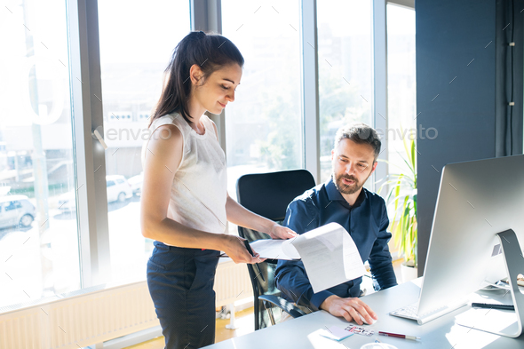 Two business people in the office working together. - Stock Photo - Images