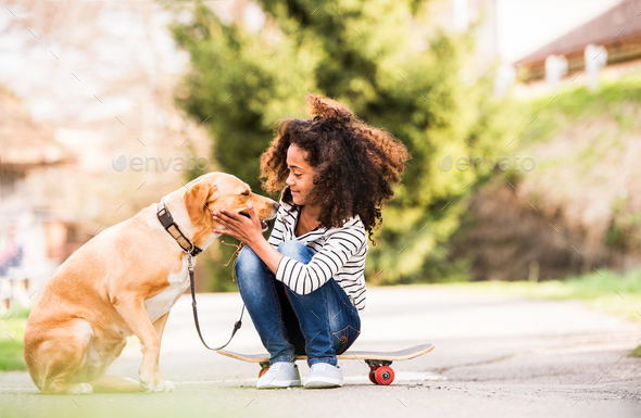 African american girl outdoors on skateboard with her dog. - Stock Photo - Images
