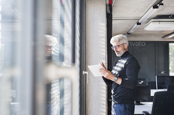 Mature businessman with tablet in the office. - Stock Photo - Images