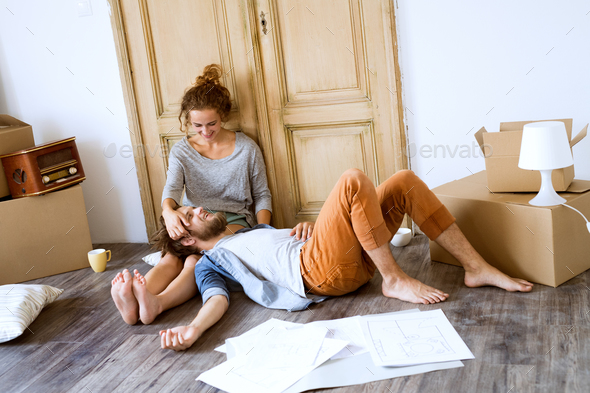 Young couple moving in new house, resting. - Stock Photo - Images