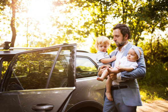 Young father with baby and toddler by the car. - Stock Photo - Images