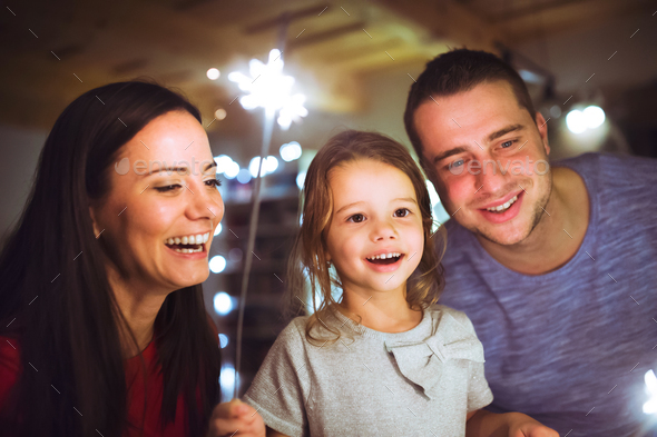Young family with sparklers at Christmas time at home. - Stock Photo - Images