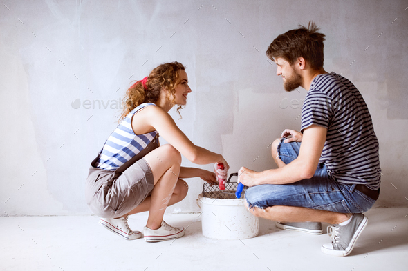 Young couple in love painting walls in their new home. - Stock Photo - Images