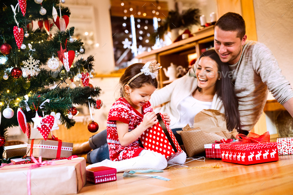 Young family with daughter at Christmas tree at home. - Stock Photo - Images