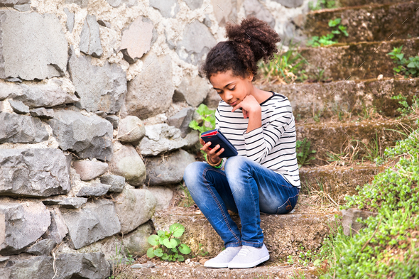Beautiful african american girl with smart phone, sitting on stairs - Stock Photo - Images
