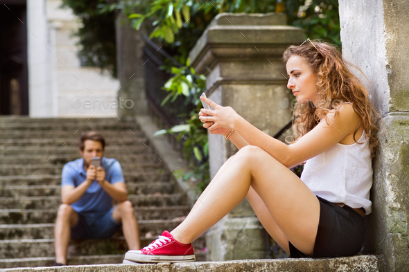Young couple with smartphones sitting on stairs in town. - Stock Photo - Images
