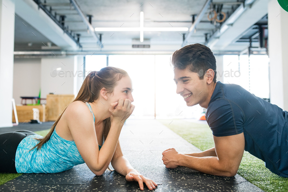 Young fit couple in gym lying on the floor, resting. - Stock Photo - Images