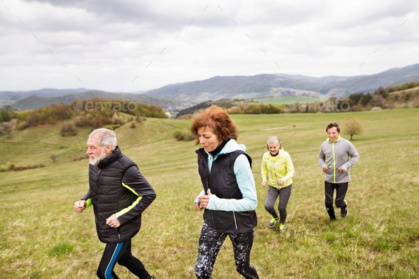 Group of seniors running outside on the green hills. - Stock Photo - Images