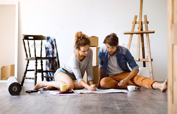 Young couple moving in new house, unpacking things. - Stock Photo - Images