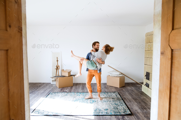 Man carrying woman in his arms, moving in new house. - Stock Photo - Images