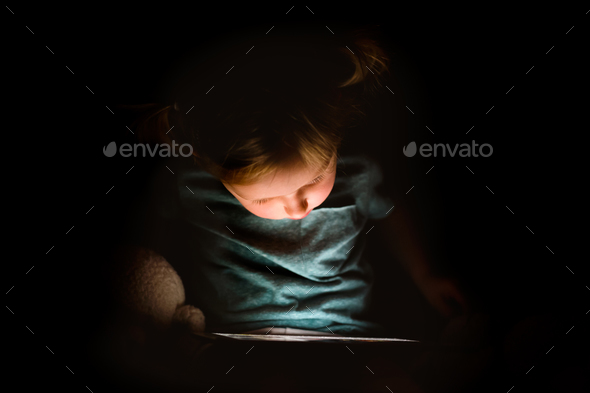 Little girl at home at night watching something on tablet. - Stock Photo - Images