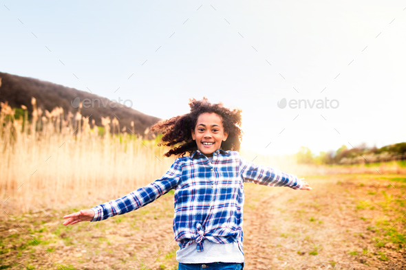 African american girl in checked shirt outdoors in field. - Stock Photo - Images