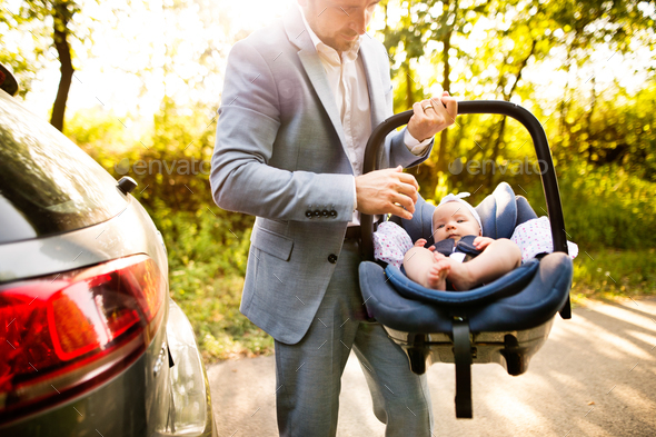 Unrecognizable man carrying his baby girl in a car seat. - Stock Photo - Images
