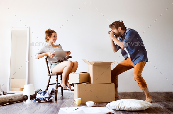 Young couple moving in new house, taking photos. - Stock Photo - Images
