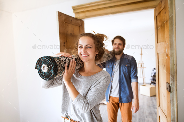 Young couple moving in new house, carrying a carpet. - Stock Photo - Images