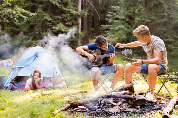 Teenagers camping in forest. Summer adventure. - Stock Photo - Images