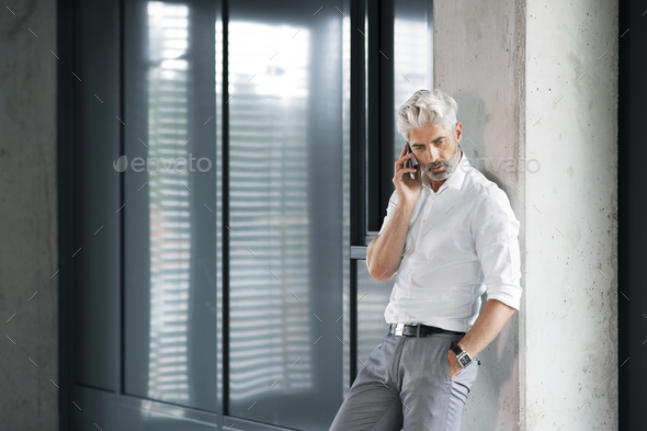 Mature businessman with smartphone in the office. - Stock Photo - Images