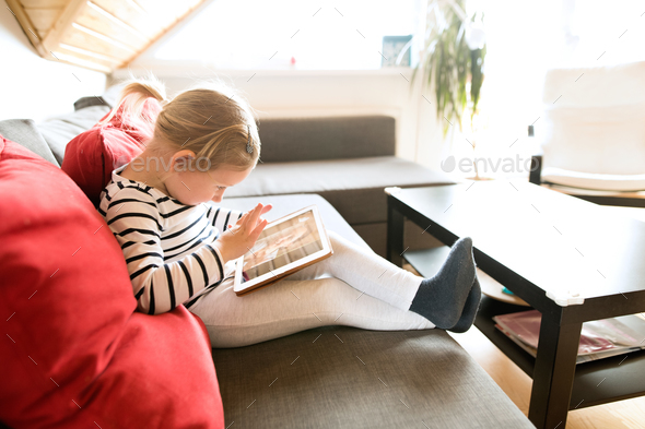 Little girl at home with tablet, video chatting with her mother. - Stock Photo - Images