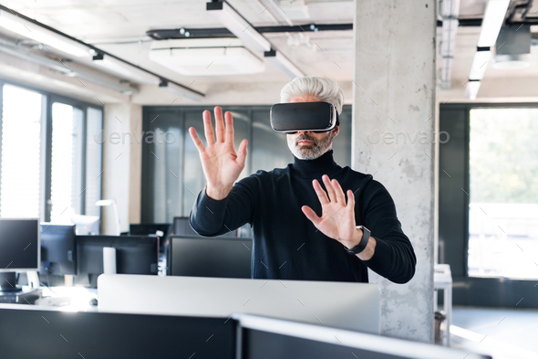 Mature businessman with VD goggles in the office. - Stock Photo - Images