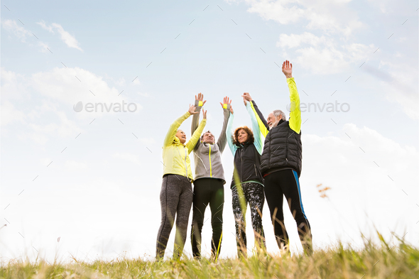 Senior runners outdoors, resting, hands in the air. - Stock Photo - Images