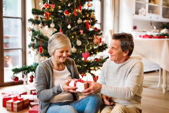 Senior Couple In Front Of Christmas Tree With Presents Stock Photo