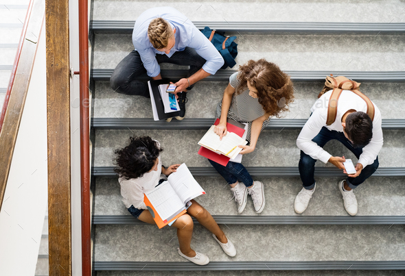 Teenage students on stairs in high school. - Stock Photo - Images