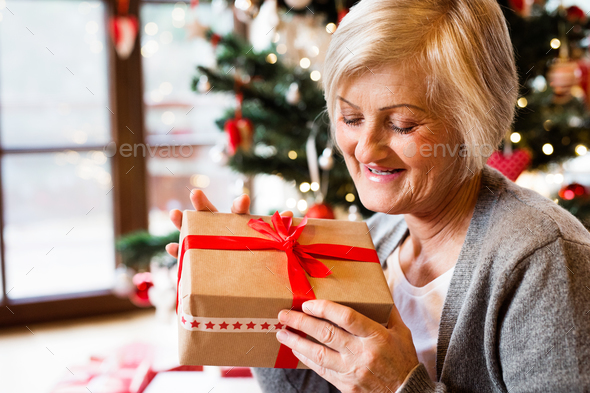 Beautiful senior woman in front of Christmas tree with present - Stock Photo - Images