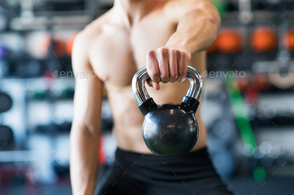 Unrecognizable young fit man in gym exercising with kettlebell. - Stock Photo - Images
