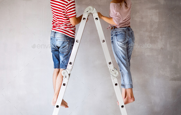 Unrecognizable couple painting walls in their house. - Stock Photo - Images