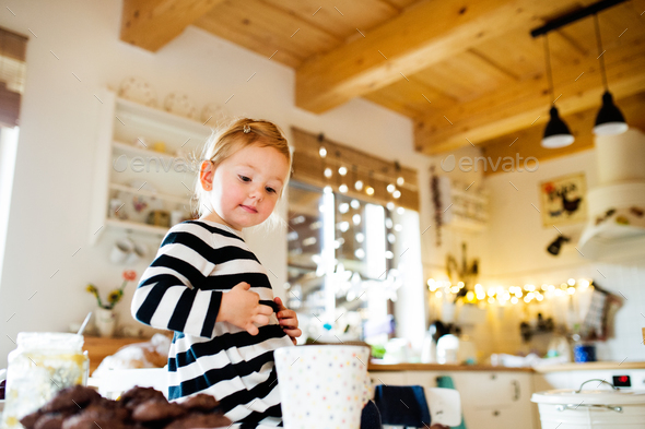 Cute little girl in striped dress sitting on kitchen table. - Stock Photo - Images
