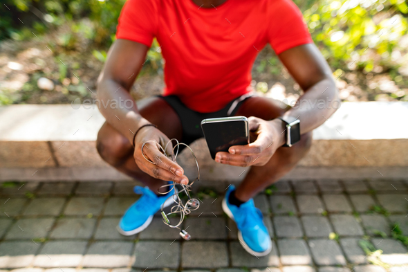 Unrecognizable runner with smart phone, listening music. - Stock Photo - Images