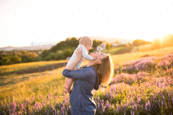 Young mother in nature with baby son in the arms. - Stock Photo - Images