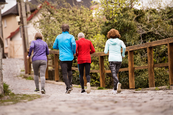 Group of seniors running outdoors in the old town. - Stock Photo - Images