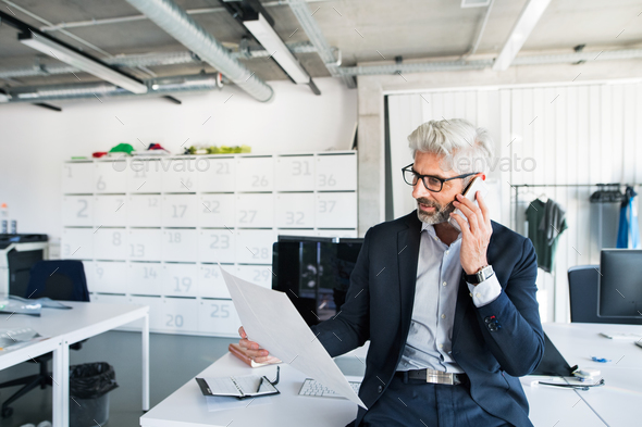 Mature businessman in the office making a phone call. - Stock Photo - Images