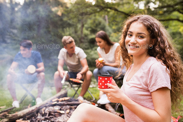 Teenagers camping, cooking meat on bonfire. - Stock Photo - Images