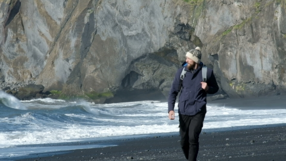 VideoHive Man with a Backpack Walking Along the Shore of Black Sand Beach in Iceland 20755004