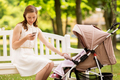 happy mother with smartphone and stroller at park - PhotoDune Item for Sale
