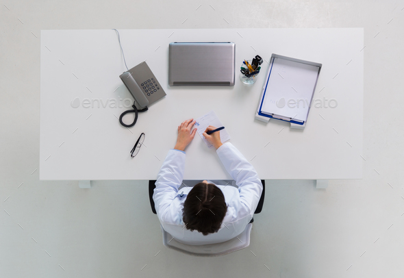 doctor writing prescription at table - Stock Photo - Images