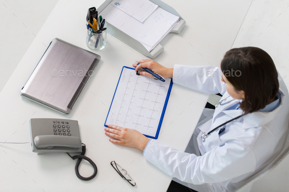 doctor with cardiogram sitting at table - Stock Photo - Images