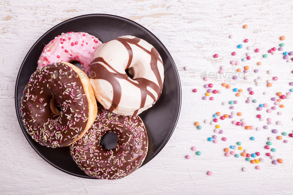 Different type of donuts on white wooden background - Stock Photo - Images