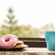 Donuts and a cup of coffee next tot the window sill - PhotoDune Item for Sale