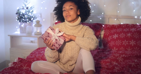 Single Woman Holding Christmas Gift in Bed