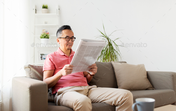 asian man in glasses reading newspaper at home - Stock Photo - Images