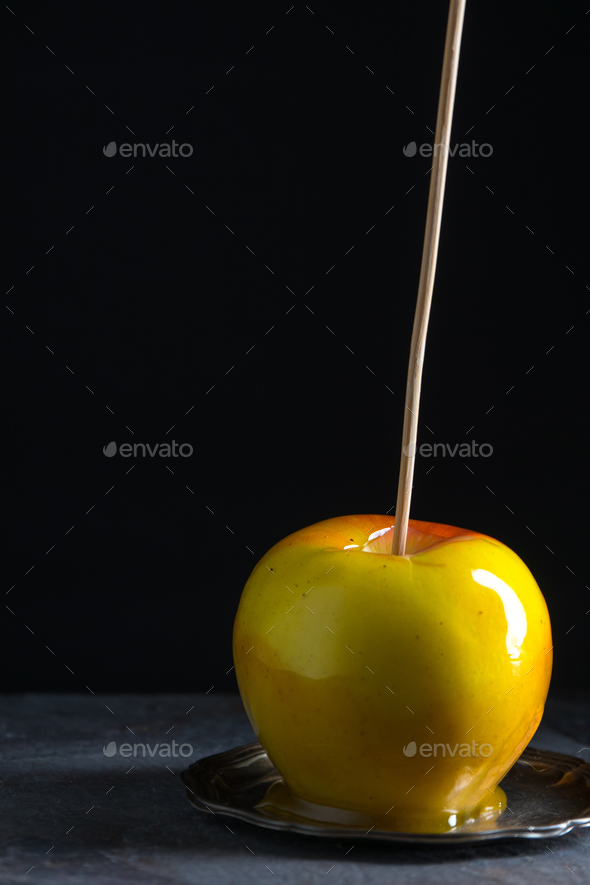 One caramel apple on a small tin plate - Stock Photo - Images
