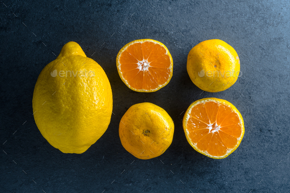Four halves of an orange and a lemon on a blue stone - Stock Photo - Images
